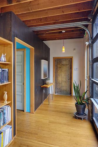 Celery - entry featuring salvaged metal door and inserted volume with restrooms and storage